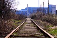 Estrada de ferro reta que vai à fábrica azul velha Fotos de Stock