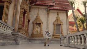 Estrada de limpeza da ajuda doce pequena da menina perto do templo de buddha Vassoura da lavagem da criança video estoque