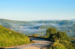A estrada de Serebryansk a Ust-Kamenogorsk na região do leste de Cazaquistão do amanhecer, Cazaquistão da montanha Imagem de Stock