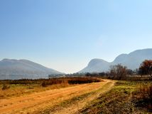 Estrada de terra ao lado do lago que conduz às montanhas Fotos de Stock