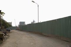 Estrada de terra ao longo de cerca de aço ondulada incluida Imagens de Stock Royalty Free