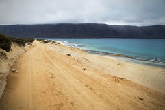Estrada de terra ao longo do mar Imagens de Stock Royalty Free