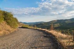 Estrada de terra através do terreno montanhoso fotografia de stock