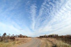 Estrada de terra com nuvens de Altocumulus Fotografia de Stock Royalty Free