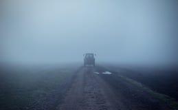Estrada de terra com o trator no dia nevoento imagens de stock