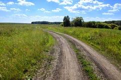 Estrada de terra do campo Céu azul e nuvens Foto de Stock Royalty Free