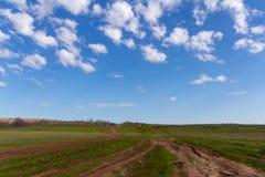 A estrada de terra do campo vai além do horizonte e das nuvens brancas no céu azul fotos de stock