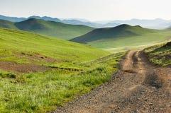 Estrada de terra do enrolamento através do estepe central do Mongolian Fotografia de Stock