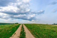 Estrada de terra em um campo Imagens de Stock
