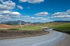Estrada de terra entre campos e montes Fotos de Stock