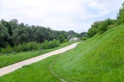 Estrada de terra entre montes e árvores no campo no verão Imagens de Stock