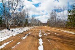 Estrada de terra nevado em um dia de inverno belamente ensolarado com os céus azuis brilhantes com nuvens inchados - na área da n fotografia de stock