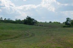 Estrada de terra rural em um monte no horizonte da grama e no azul nebuloso t foto de stock