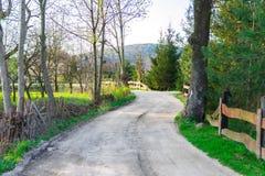 Estrada de terra rural, vila bonita no verão, a estrada sob a cerca caída velha imagens de stock royalty free