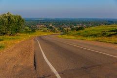 A estrada de torção do monte à exploração agrícola Fotografia de Stock Royalty Free