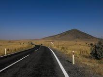 Estrada do alcatrão que conduz com uma paisagem estéril Foto de Stock Royalty Free