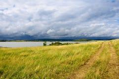 Estrada do campo perto do lago após uma chuva Fotos de Stock