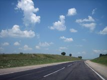 A estrada do carro nas quebras entra distante na distância em um dia ensolarado brilhante fotografia de stock royalty free