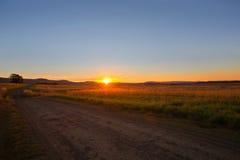 Estrada do cascalho do por do sol fotografia de stock royalty free