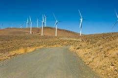 Estrada do cascalho entre turbinas de vento. imagens de stock