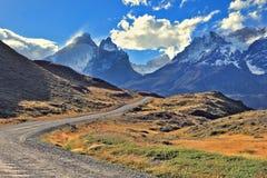 A estrada do cascalho vai às montanhas cobertos de neve imagem de stock royalty free