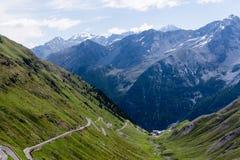 Estrada do cume cercada por montanhas altas azuis do cume Descida íngreme do dello Stelvio de Passo em Stelvio Natural Park Fotografia de Stock Royalty Free