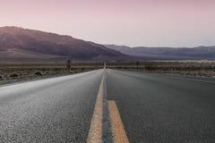Estrada do deserto no por do sol Imagens de Stock Royalty Free