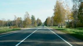 Estrada do outono para a condução de carros entre as árvores em Bielorrússia filme