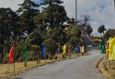 Estrada e escadas decoradas com as bandeiras coloridas ao monastério de Druk Wangyel da passagem de Dochala em Butão fotografia de stock royalty free