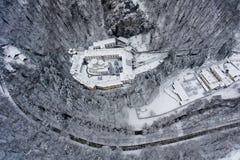 A estrada e o monastério do inverno cercados por árvores dispararam de um zangão acima imagem de stock