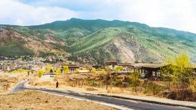 Estrada e vila com montanha alta e a nuvem enorme acima de Thimphu Fotos de Stock Royalty Free
