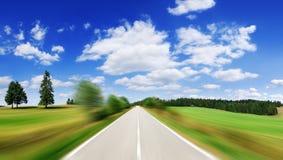 Estrada entre campos verdes com efeito do borrão de movimento fotografia de stock