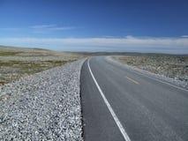 Estrada entre planícies rochosas em Noruega Fotos de Stock Royalty Free