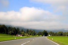 A estrada entre prados verdes com as montanhas nas nuvens no fundo no dia ensolarado Foto de Stock Royalty Free