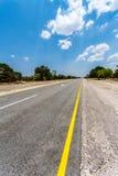 Estrada infinita com céu azul Imagens de Stock Royalty Free