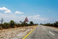 Estrada infinita com cruzamento dos elefantes do céu azul e do sinal Fotografia de Stock Royalty Free