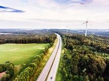 Estrada na floresta verde, moinhos de vento, céu nebuloso netherlands fotos de stock