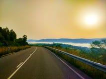 Estrada na manhã, com as montanhas sobre nuvens e o nascer do sol em t foto de stock