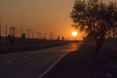 A estrada na névoa Por do sol O sol imagem de stock