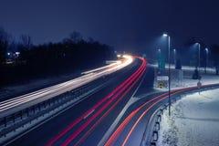 Estrada na noite nevado com as fugas de luz do tráfego entrante e que parte imagens de stock royalty free