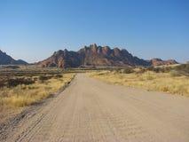 Estrada namibiana do cascalho com as montanhas no fundo imagens de stock royalty free