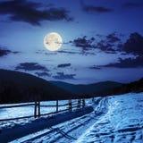 Estrada nevado à floresta conífera nas montanhas na luz de lua Imagem de Stock
