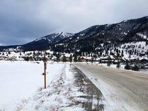 Estrada nevado da montanha pelas montanhas Fotografia de Stock