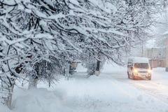 Estrada nevado do inverno com o carro perto das construções Fotos de Stock Royalty Free