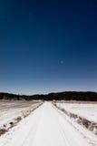 Estrada nevado longa e céu estrelado do espaço livre na luz de lua imagem de stock