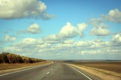Estrada no dia ensolarado do outono com a nuvem no céu azul Imagem de Stock