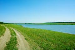 Estrada no gramado verde pelo lago imagens de stock