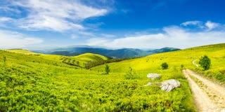 Estrada no prado do montanhês no panorama da montanha no nascer do sol Fotos de Stock Royalty Free