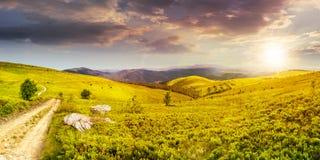 Estrada no prado do montanhês no panorama da montanha no por do sol Fotografia de Stock