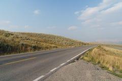 Estrada nos montes e no prado Fotos de Stock Royalty Free